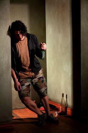 lean: Drunk young man leaning on a wall with beer bottle Stock Photo
