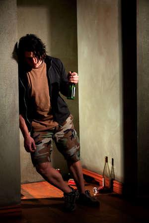 ubriaco: Giovane ubriaco, appoggiandosi su un muro con una bottiglia di birra