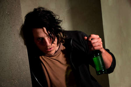 impaired: Drunk young man leaning on a wall with beer bottle Stock Photo