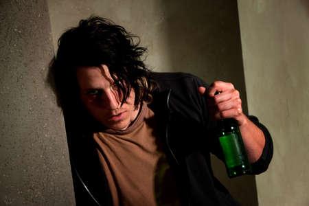 Opgedronken jonge man leunend tegen een muur met bier fles