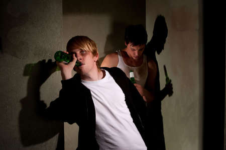 impaired: Drunk young men in hallway with bottles Stock Photo