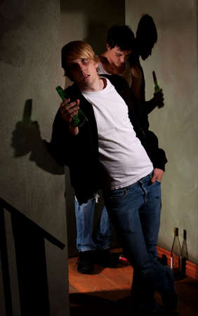 Drunk young men in hallway with bottles photo