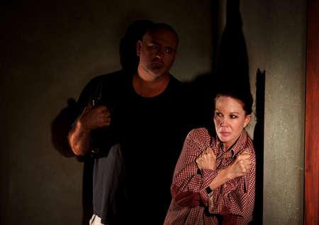 협박 남자와 그녀의 뺨에 상처와 복도에있는 여자 스톡 콘텐츠