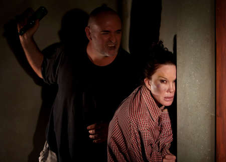 Woman in hallway with bruise on her cheek with menacing man Stock Photo - 6662546