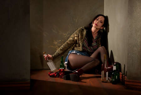 drunk woman: Woman surrounded by booze bottles in a hallway