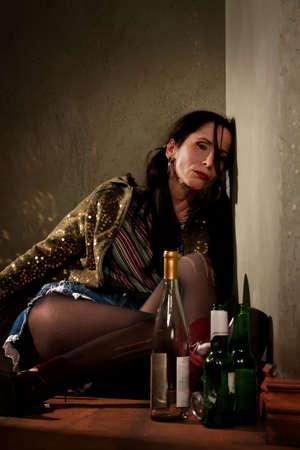 Vrouw omringd door drank flessen in een gang