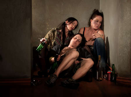 Partygoers surrounded by booze bottles in a hallway photo
