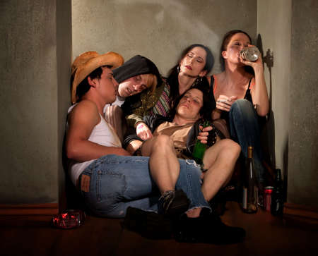 Partygoers surrounded by booze bottles in a hallway Stock Photo