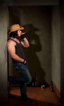 Smoking man in cowboy hat leaning on wall photo