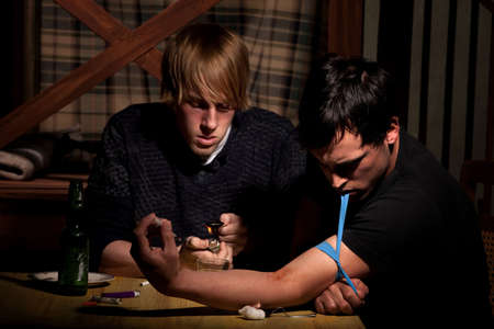 opiate: Two men with heroin cooking in a bent spoon Stock Photo