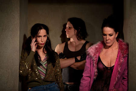 Frightened prostitutes in hallway with pimp photo