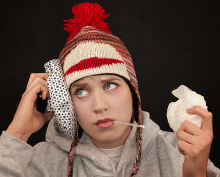 Sick young woman with thermometer and monkey cap photo