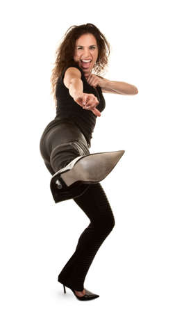 Tough woman in high heels kicking at camera Reklamní fotografie