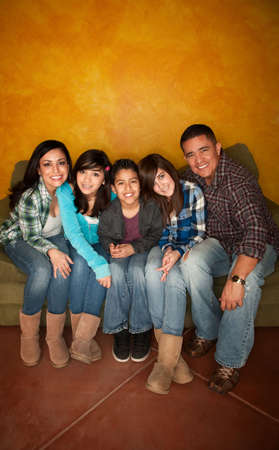 family sofa: Attractive Hispanic Family Sitting on a Green Couch