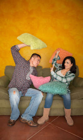 Hispanic couple on couch play fighting with pillows