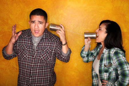 Aantrekkelijke Hispanics man en vrouw communiceren via tin blikjes
