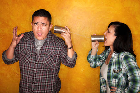 Attractive Hispanic man and woman communicate through tin cans
