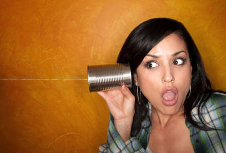 telephone: Attractive Hispanic woman with tin can telephone