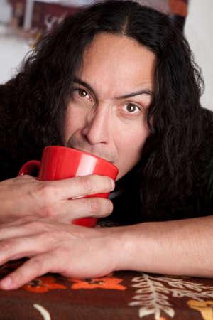 cradling: Tired Latino man cradling red coffee cup