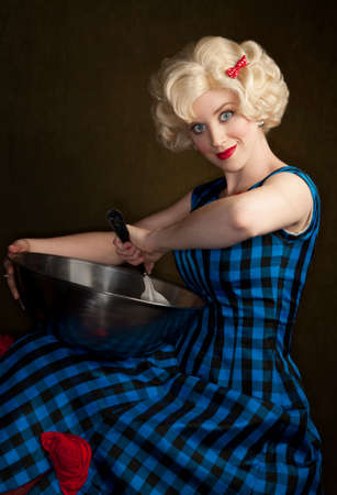 eccentric: Pretty retro blonde woman in vintage 50s dress with bowl and spoon Stock Photo