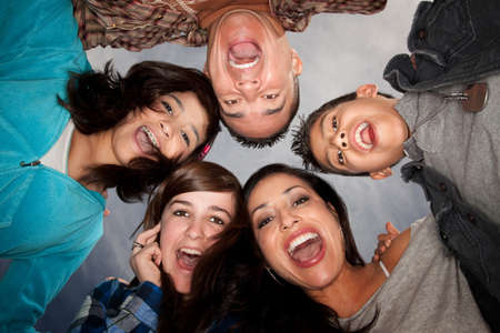 cute braces: Looking up at Hispanic family in huddle Stock Photo
