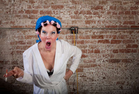 cranky: Upset lady with pink curlers and white robe Stock Photo