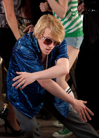 Blonde Haired man dancing low at a 1970s Disco Music Party photo