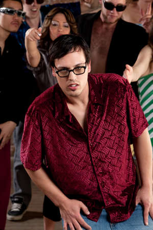 wimp: Nerdy young man stumbling at a 1970s Disco Music Party