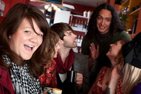 Woman in front of diverse friends in a coffee house photo