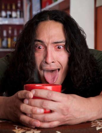 cradling: Desperate Latino man cradling red coffee cup