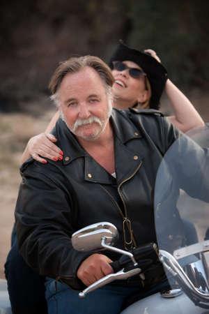 Fun couple riding a white motorcycle outside photo