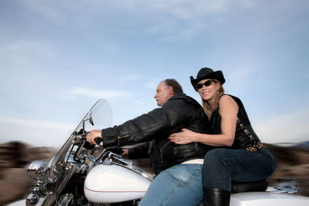 Couple riding a motorcycle outside during sunset photo