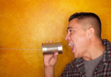 tin cans: Aantrekkelijke Hispanic man met blikje telefoon Stockfoto