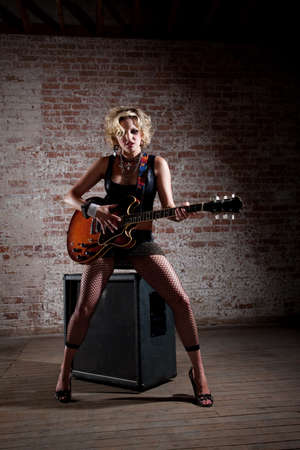 Female punk rock guitarist alone in a warehouse with a large speaker