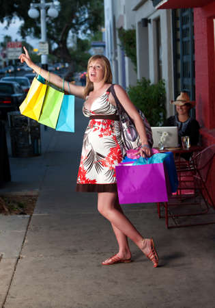 frantic: Pregnant woman with shopping bags waving down a taxi on the street