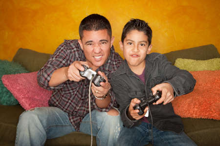 Attractive Hispanic Man and Boy Playing a Video Game with Handheld Controllers photo