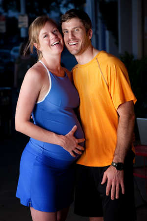 Pregnant woman and husband in fitness attire on the street photo
