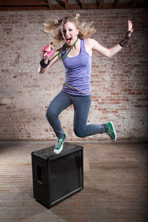 Young punk rocker jumps from a speaker in front of a brick background photo
