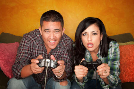 Attractive Hispanic Couple Playing a Video Game with Handheld Controllers photo