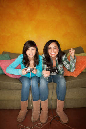 Attractive Hispanic Woman and Girl Playing a Video Game with Handheld Controllers Stock Photo - 7085346