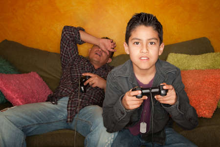 dissapointed: Attractive Hispanic Man and Boy Playing a Video Game with Handheld Controllers