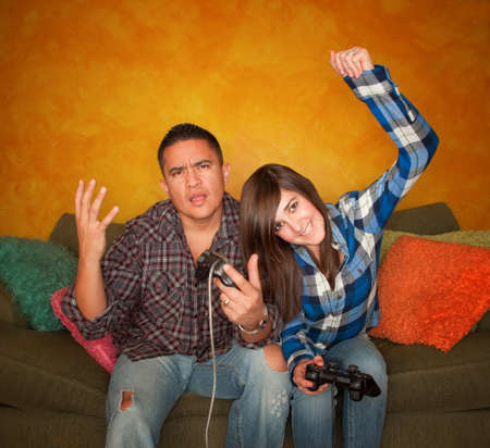 Attractive Hispanic Man and Girl Playing a Video Game with Handheld Controllers photo