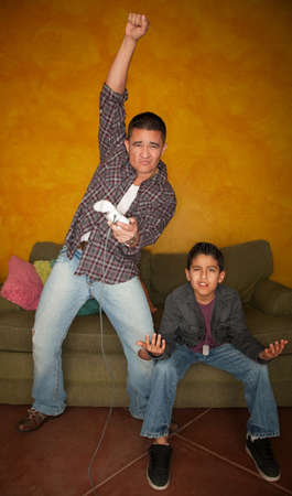 Handsome Hispanic man playing Video game with bored young boy photo