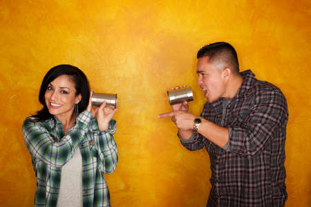 tin can telephone: Attractive Hispanic man and woman communicate through tin cans