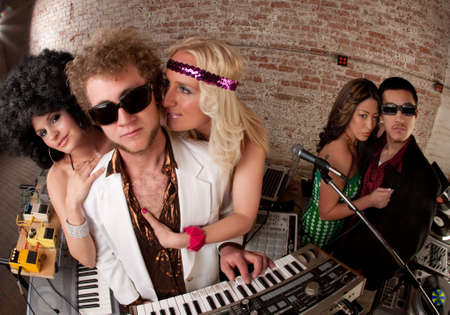 Handsome DJs surrounded by ladies at a 1970s Disco Music Party photo