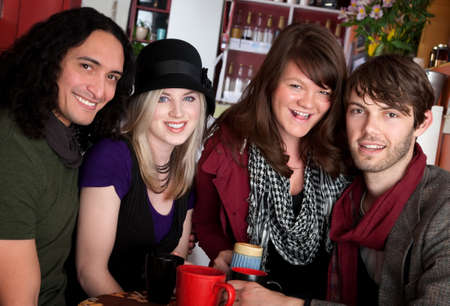 Two couples smiling together in a cafe photo
