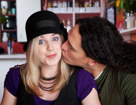 Caucasian and Native American couple kissing at a cafe photo