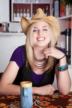 Smiling blonde woman with cowboy hat in a cafe photo