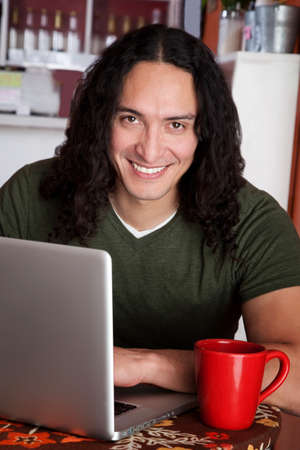 Handsome Native American man with laptop and red mug photo