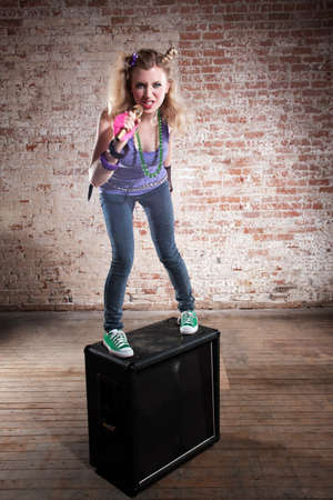 Young punk rocker on a speaker in front of a brick background photo